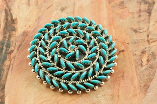 Stunning Pendant/Brooch featuring Genuine Sleeping Beauty Turquoise set in Sterling Silver. Beautiful Petit Point Design. Many days of painstaking work went into creating this Southwestern Art Masterpiece.  Created by Master Zuni Artists Octavious and Irma Seowtewa.  Signed by the artists. Free 18&quot; Sterling Silver Chain with purchase of pendant. The Zuni Pueblo is located in New Mexico, Land of Enchantment.